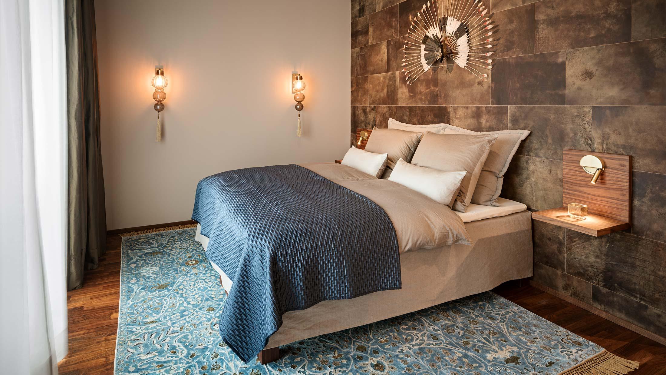 Penthouse Fünf Morgen: Luxuriöses Schlafzimmer mit metallfreiem Bio Boxspringbett und markanter Lederwand
