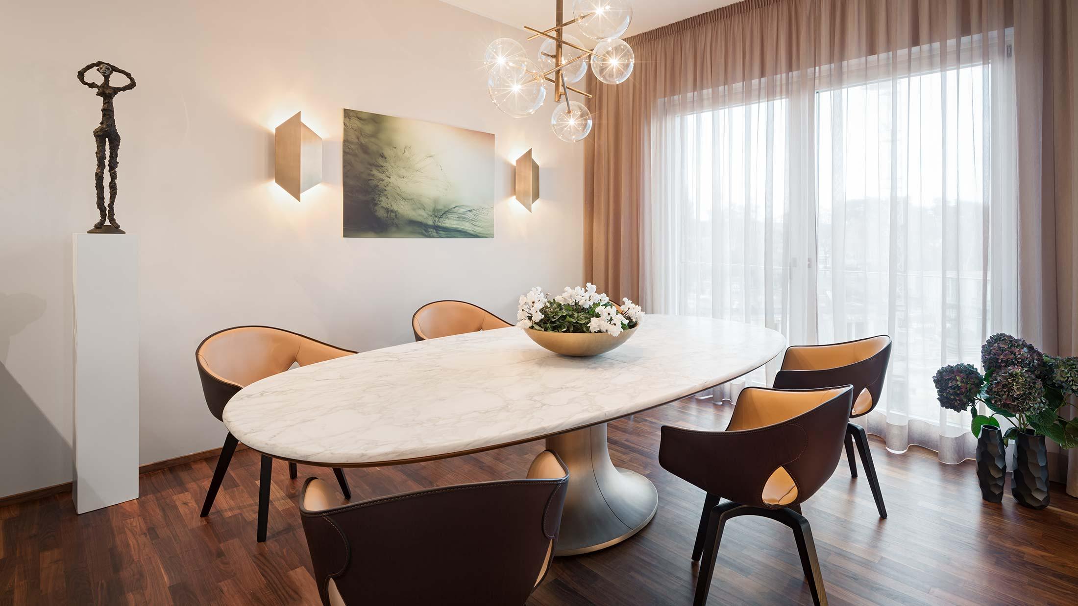 Penthouse Fünf Morgen: Esszimmer Tisch mit markantem Bronzefuß und Platte aus edlem Marmor Calacatta Oro